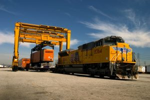 Train getting loaded with container by machinery and logistics software