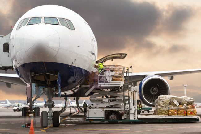cargo loaded onto airplane using logistics software on cloudy day