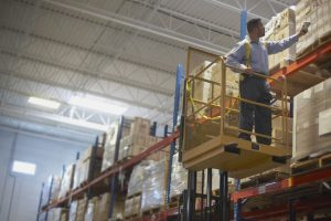 Warehouse worker checking boxes using transportation management system