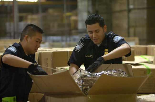 US customs agent looking through boxes with the process management by a logistics management system