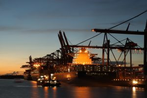 Container ship at night at port powered by logistics software