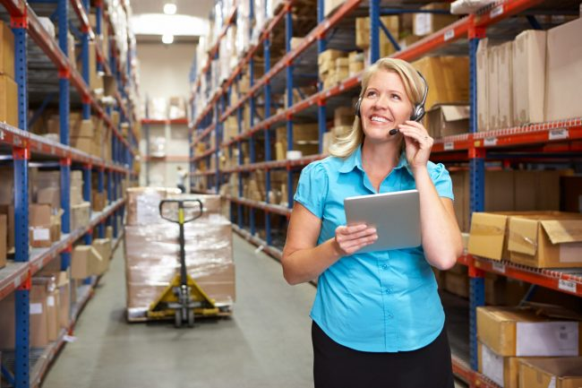 Lady in warehouse with boxes using logistics software on tablet to manage supply chain