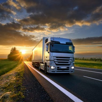 Truck with trucking software driving on the asphalt road in rural landscape at sunset with dark clouds