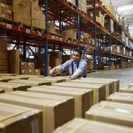 worker tagging boxes in warehouse for processing by logistics management system